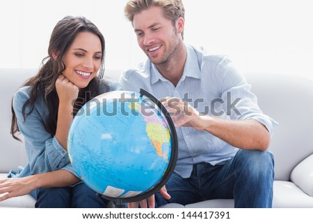 Cheerful couple looking at a globe in the living room - stock photo