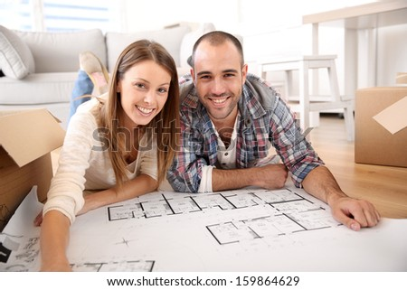 Cheerful couple looking at construction house plan  - stock photo