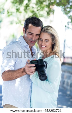 Cheerful couple looking in camera while standing outdoors