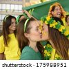 Cheerful couple of Brazilian girlfriends soccer fans kissing each other celebrating victory. - stock photo