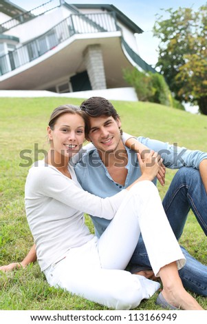 Cheerful couple of lovers laying in garden