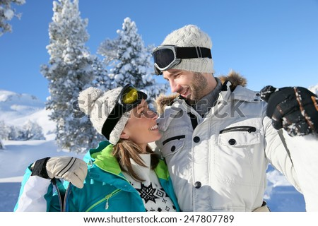 Cheerful couple of skiers looking at each other's eyes - stock photo