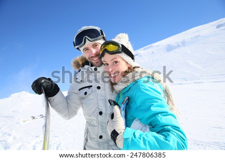 Cheerful couple of skiers ready to go down ski slope - stock photo