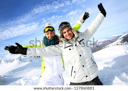 Cheerful couple of skiers stretching arms up
