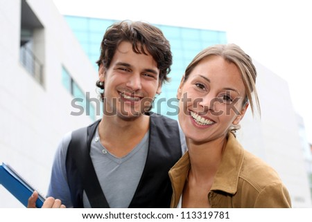 Cheerful couple of students standing on college campus - stock photo