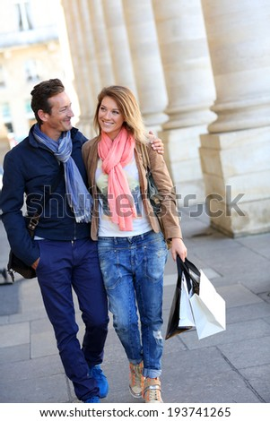 Cheerful couple of tourists in town doing shopping - stock photo
