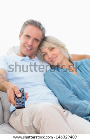 Cheerful couple on their couch watching tv at home in living room - stock photo