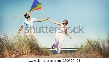 Cheerful Couple Playing Kite by the Beach Concept - stock photo
