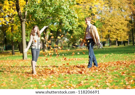 Cheerful couple playing with autumn leaves - stock photo