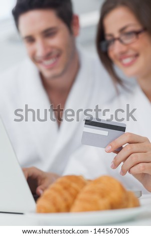 Cheerful couple purchasing online while having breakfast - stock photo
