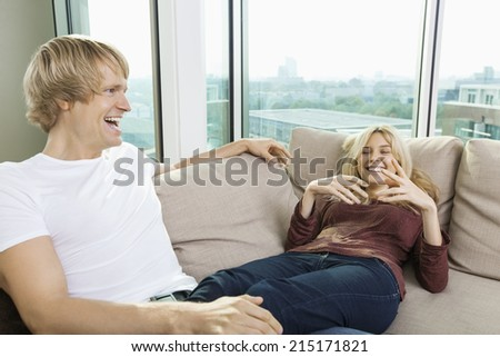 Cheerful couple relaxing on sofa at home - stock photo