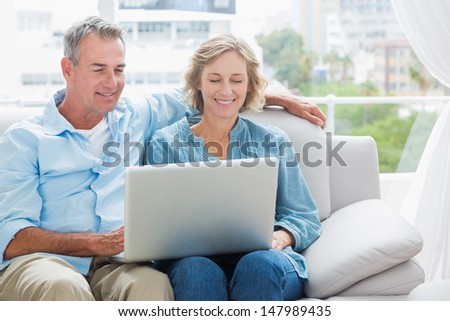 Cheerful couple relaxing on their couch using the laptop at home in the sitting room