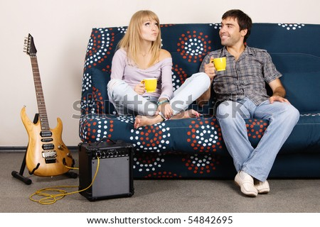 Cheerful couple resting on a sofa - stock photo