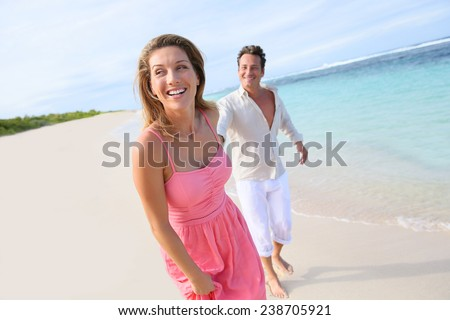 Cheerful couple running on a sandy beach - stock photo