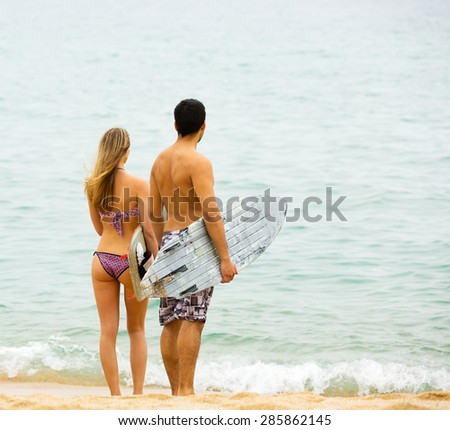 Cheerful couple running on the beach with surf boards