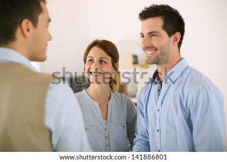 Cheerful couple shaking hand to salesman - stock photo