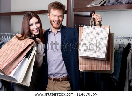 Cheerful couple show their purchases after shopping - stock photo