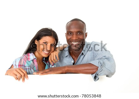 Cheerful couple showing message on whiteboard - stock photo