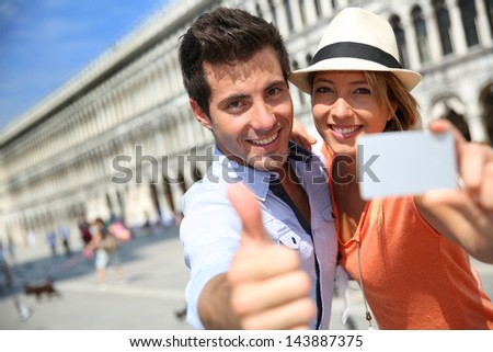 Cheerful couple showing tourist pass in Piazza San Marco - stock photo