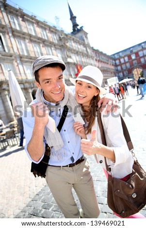 Cheerful couple showing visitor pass of Madrid - stock photo