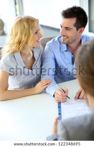 Cheerful couple signing property contract with real-estate agent - stock photo