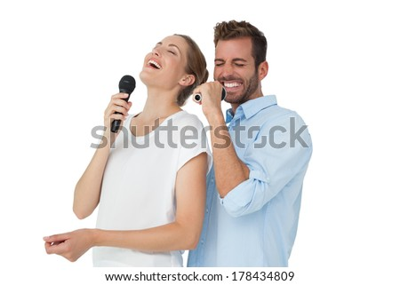 Cheerful couple singing into microphones over white background - stock photo