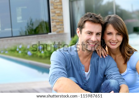 Cheerful couple sitting in front of new house - stock photo