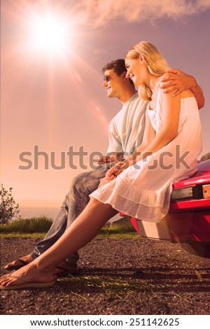 Cheerful couple sitting on their cabriolet car hood to admire the panorama - stock photo