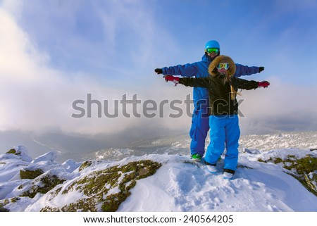 Cheerful couple snowboarders standing on the mountain  - stock photo
