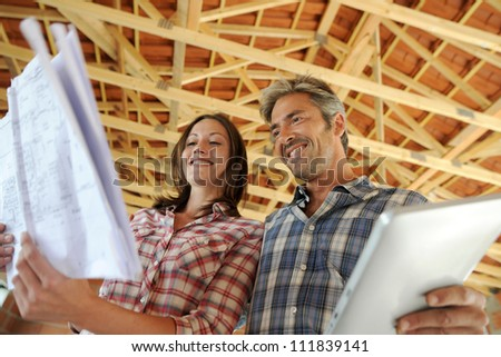 Cheerful couple standing inside house under construction - stock photo