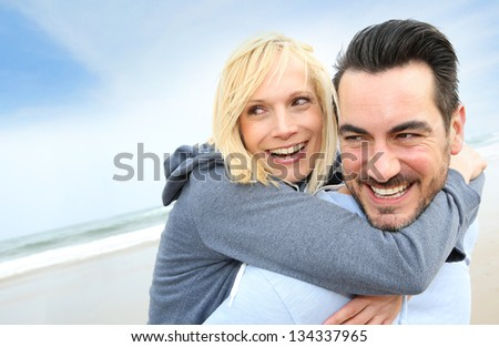Cheerful couple standing on the beach - stock photo