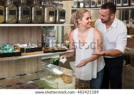 cheerful couple taking various candied fruits in store with ecological goods