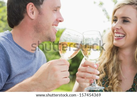 Cheerful couple toasting with white wine and looking at each other - stock photo