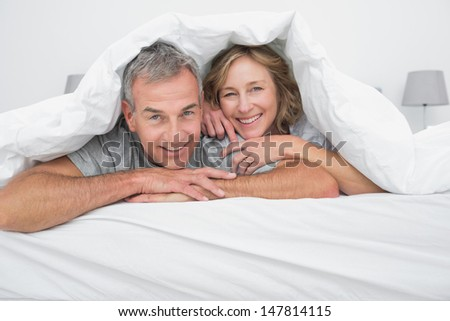 Cheerful couple under the duvet smiling at camera in bedroom at home