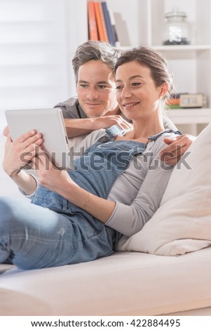 cheerful couple using a tablet at home, the young woman is pregnant, she si lying on a white couch and his husband look the tablet over her shoulder - stock photo