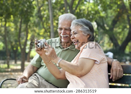 Cheerful couple using digital camera at park - stock photo