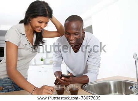 Cheerful couple using smartphone while taking coffee