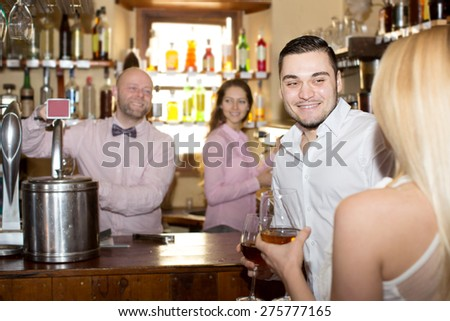 Cheerful couple waiting for table in restaurant and drinking wine at tavern. Focus on the man - stock photo