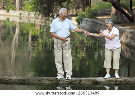 Cheerful couple walking on narrow bridge at park - stock photo