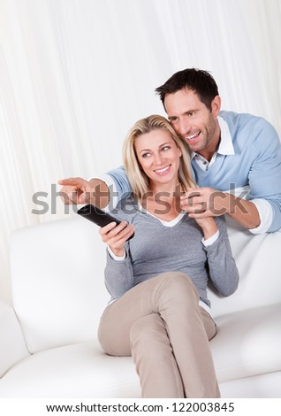 Cheerful couple watching TV sitting at sofa - stock photo