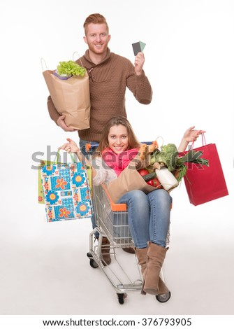 Cheerful couple with a shopping trolley isolated over white background. Man and woman with many bags full of groceries. - stock photo