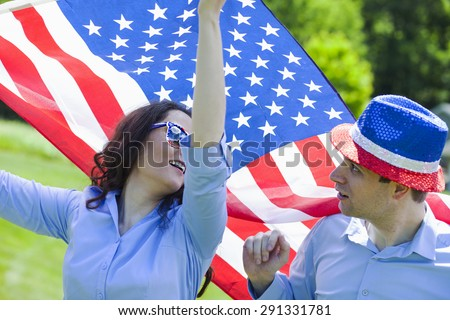 Cheerful couple with American flag for july 4th while patriotic holiday
