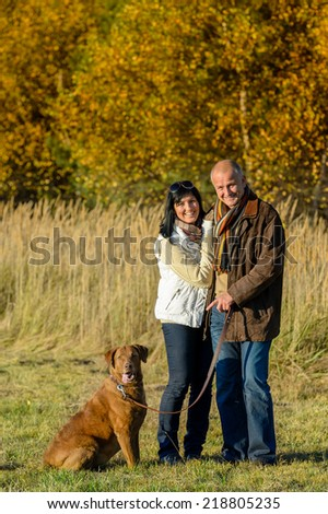Cheerful couple with dog in park autumn sunset - stock photo
