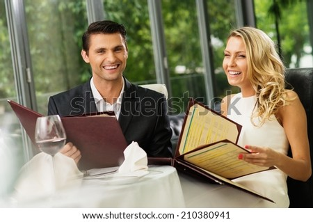 Cheerful couple with menu in a restaurant  - stock photo