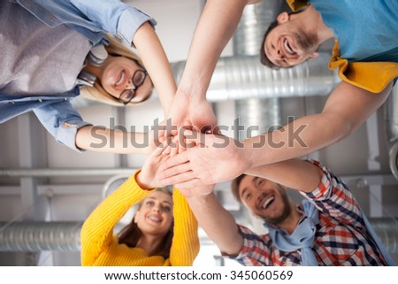 Cheerful creative team is joining hands with joy. They are working in cooperation with joy. The men and women are standing and smiling - stock photo