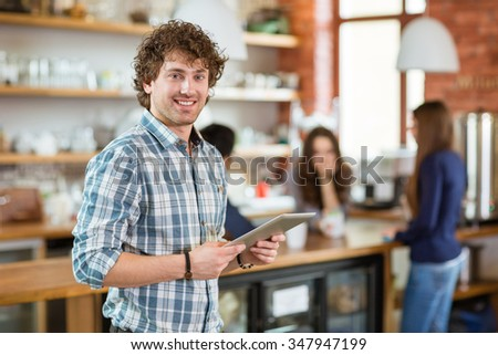Cheerful curly young guy in plaid shirt using tablet in cafe - stock photo