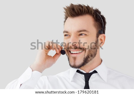 Cheerful customer service representative. Handsome young man in formalwear and headset looking away and smiling while standing against grey background - stock photo