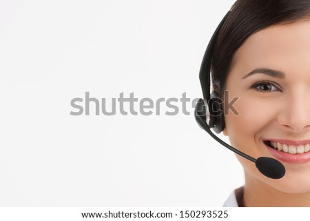 Cheerful customer service representative. Portrait of beautiful young female customer service representative in headset looking at camera and smiling while isolated on white - stock photo