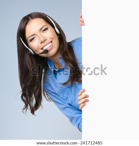 Cheerful customer support phone operator in headset showing blank signboard with area for copyspace or product, against grey background - stock photo