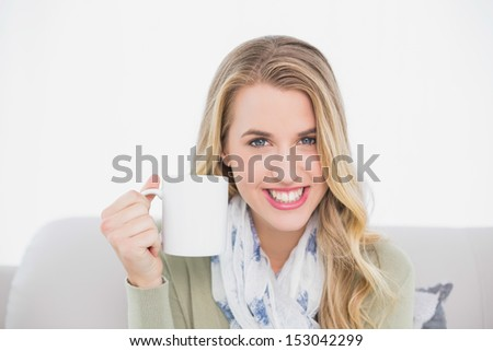 Cheerful cute blonde holding cup of coffee sitting on cosy sofa in bright living room